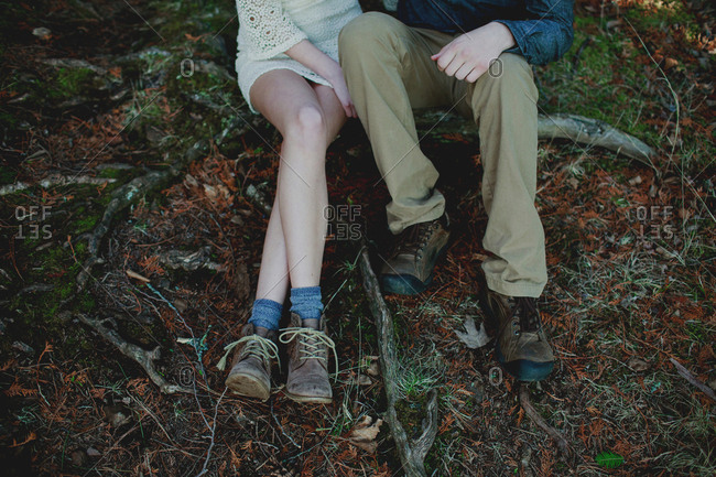 Feet of couple sitting in the woods together
