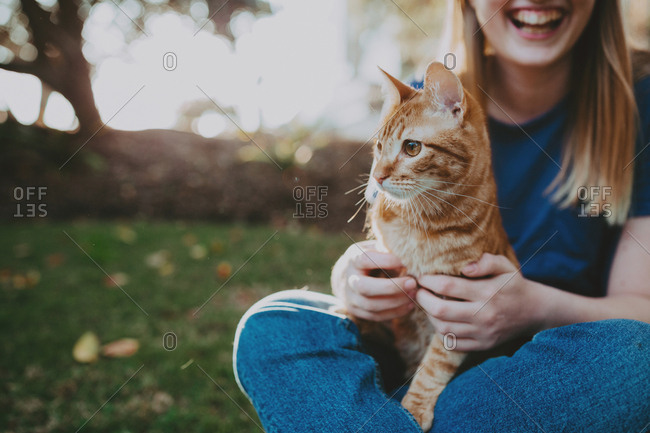Young woman holding orange cat