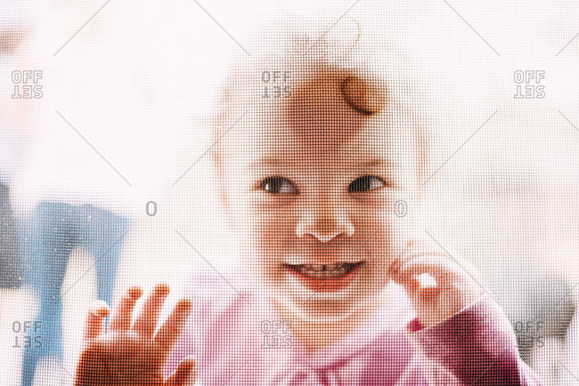 Young girl pressing face against screen