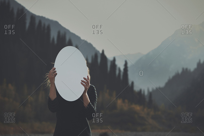Woman holding mirror in front of face stock photo OFFSET