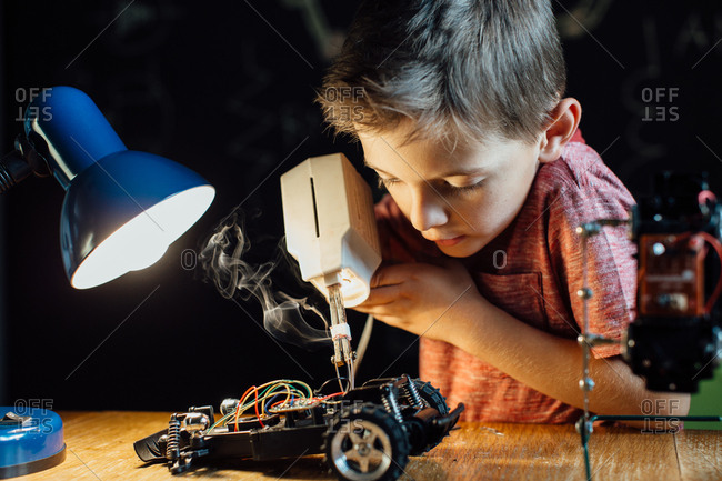 Portrait of a clever young school boy soldering metal parts of his toy car together