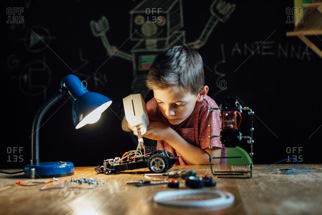 Portrait of a smart schoolboy soldering in the evening at home