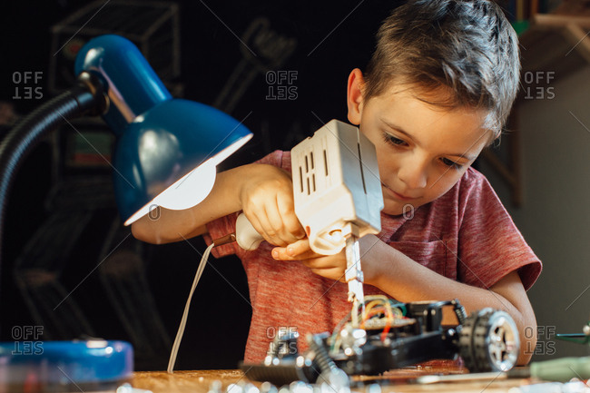 Portrait of a smart boy learning how to solder at home