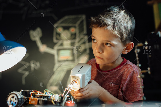 Portrait of a smart schoolboy soldering metal parts of his toy car together at home