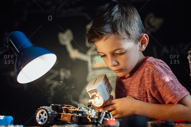 Portrait of a skilled young boy working with a soldering gun