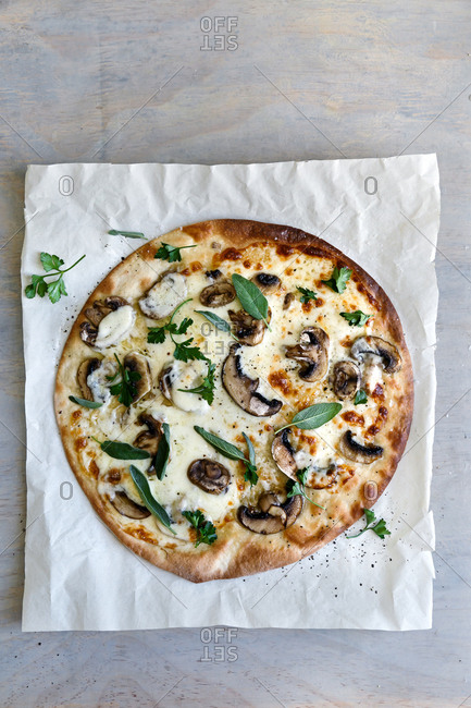 Pizza on baking paper with mushrooms and herbs
