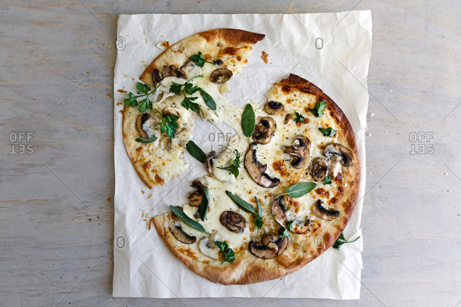 Pizza with mushroom and herbs, torn