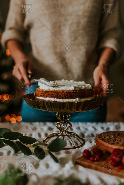 Woman putting cream on cake panes making naked cake with blurred Christmas tree in the background