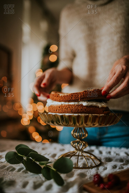 Woman putting layers of cake panes and making winter inspired naked cake with Christmas tree in the background