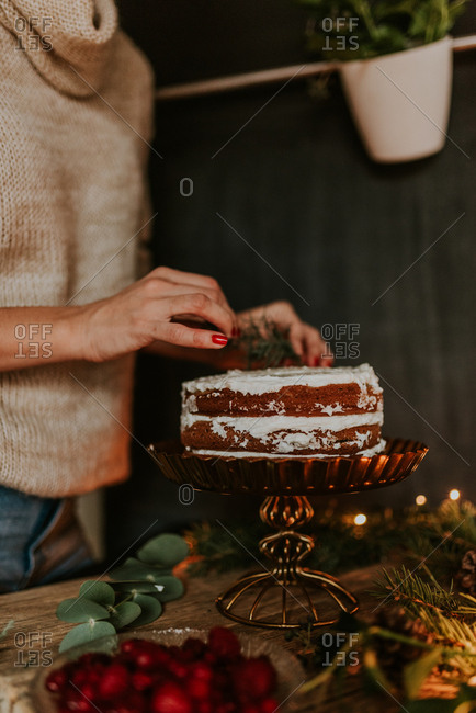 Woman decorating winter inspired naked cake with frozen strawberries and red currant