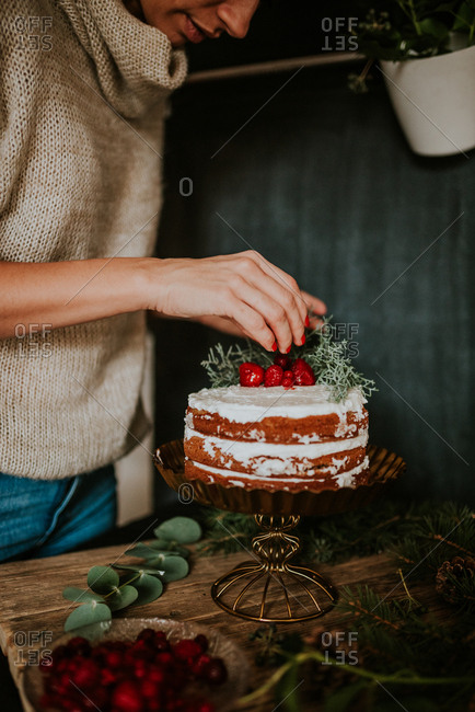 Woman decorating winter inspired naked cake with frozen strawberries and redcurrant
