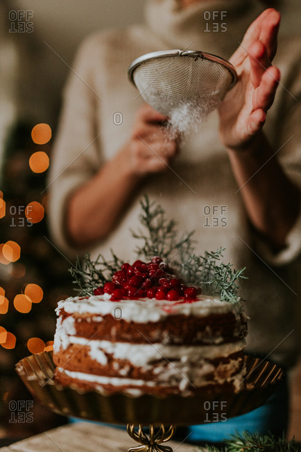 Woman decorating winter inspired naked cake with powdered sugar with Christmas tree in the background