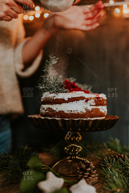 Woman decorating winter inspired naked cake with powdered sugar with Christmas lights in the background