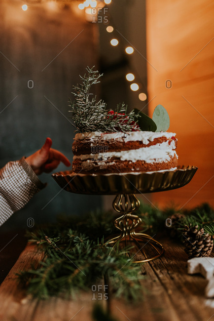 Little girl dipping finger in naked cake placed on gold pedestal with Christmas lights in the background