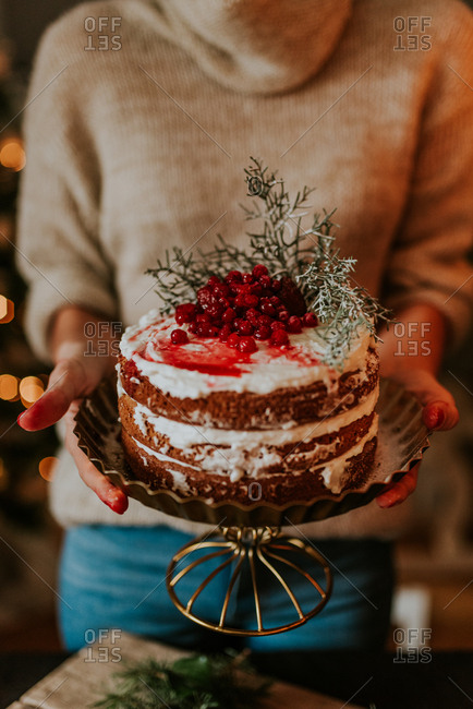 Woman holding naked cake on a gold pedestal decorated with strawberries and redcurrant with Christmas lights in the background