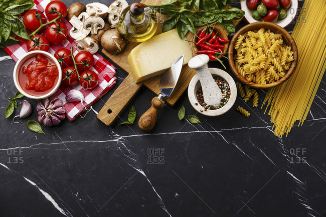 Italian food ingredients with Olives, pasta Spaghetti, Oil, Parmesan cheese, Brown mushroom, Tomato, Garlic, Basil, Chilli pepper and spices on dark marble background copy space