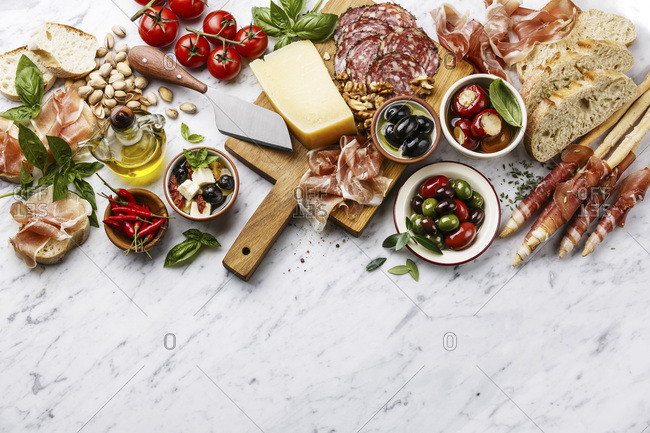Italian snacks food with Ham, Sliced bread Ciabatta, Olives, Parmesan cheese, Grissini bread sticks, Feta cheese with dried tomatoes and Sausage on white marble background copy space