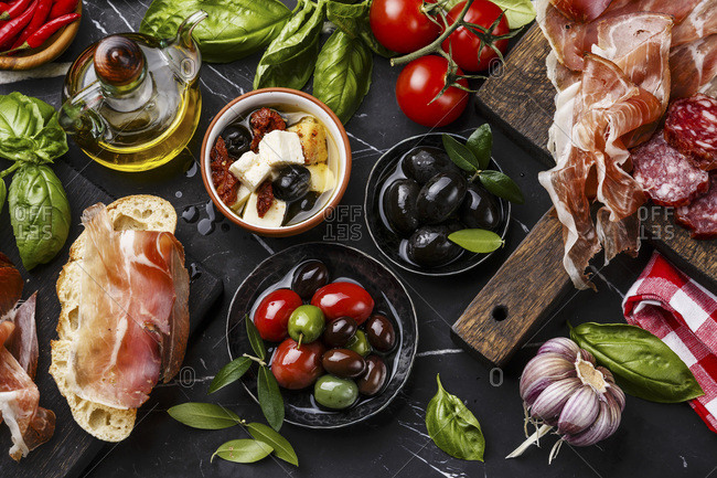 Italian snacks food with Ham, Sliced bread Ciabatta, Olives, Oil, Tomatoes, Garlic, Basil and Sausage on dark marble background