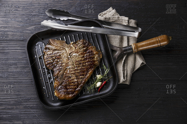 Grilled Dry Aging T-bone steak in grill iron pan and tongs on black burned wooden background