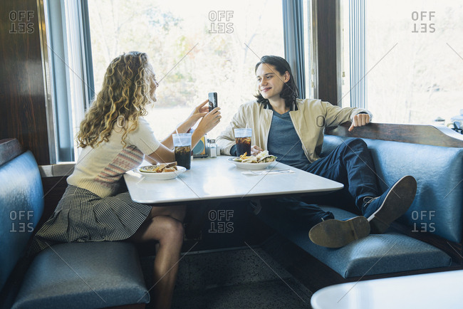 Happy young woman photographing boyfriend at table in diner