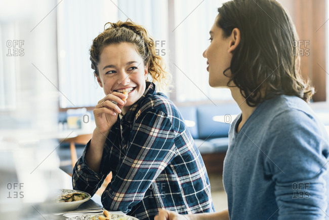 Happy young woman eating while looking at boyfriend in restaurant