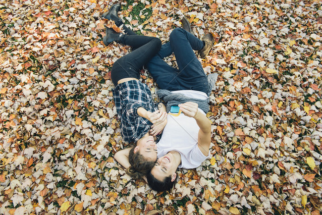 High angle view of loving young couple taking selfie through smartphone while lying on autumn leaves in forest