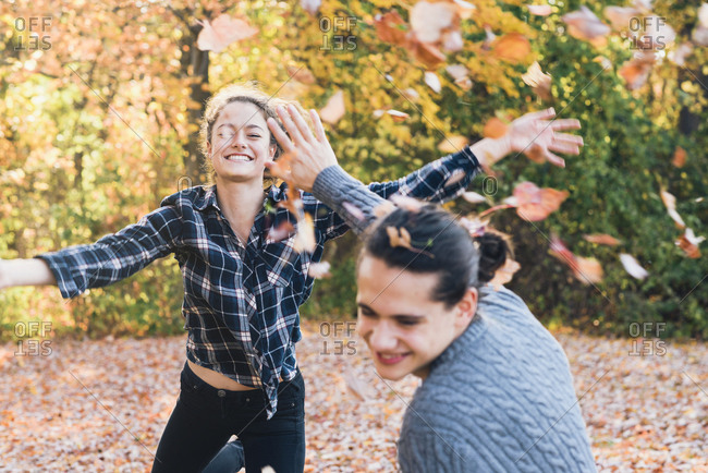 Happy playful young woman throwing autumn leaves on man in forest