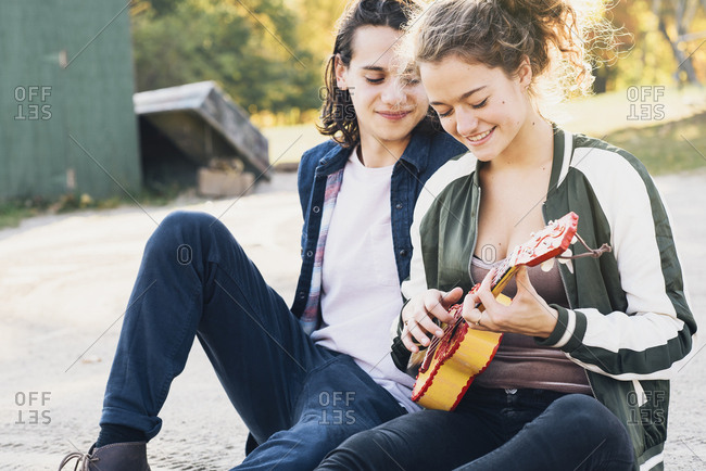 Smiling young woman playing ukulele with boyfriend
