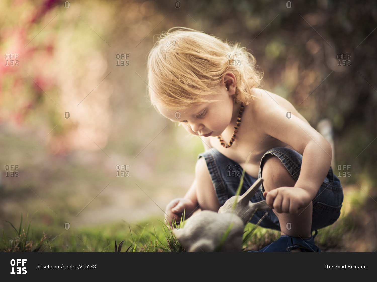 cute shirtless boy crouching while looking at toy rabbit in