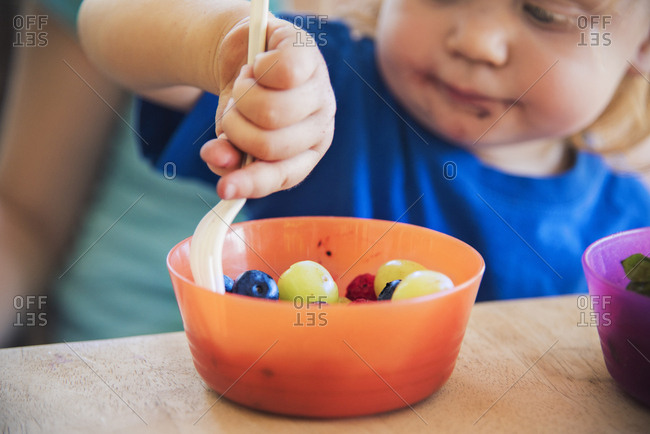 Little boy eating grapes from bowl at table