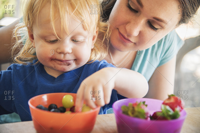 Close-up of young mother looking at baby boy having grapes at table