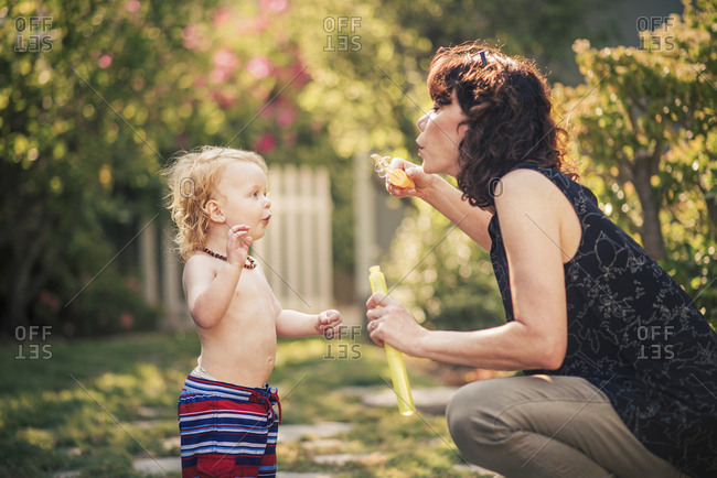 Cute boy looking at grandmother blowing bubbles from wand in backyard