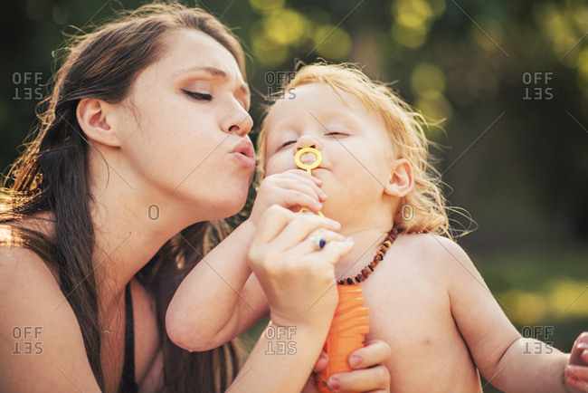 Young woman with son blowing bubble from wand in park