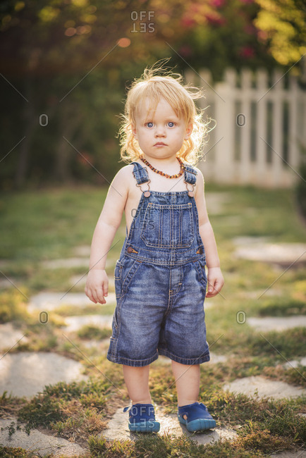 Full length portrait of cute boy in denim overalls standing in yard