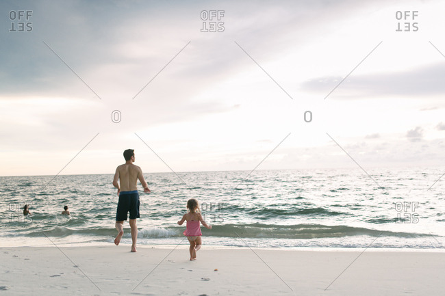 Dad running to sea with girl