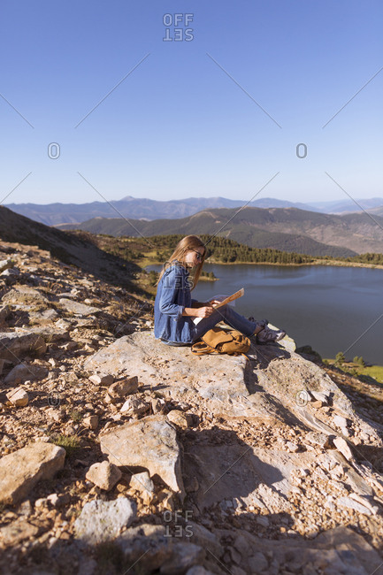 Woman on mountain overlook with map