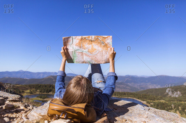 Woman lying on mountain with map