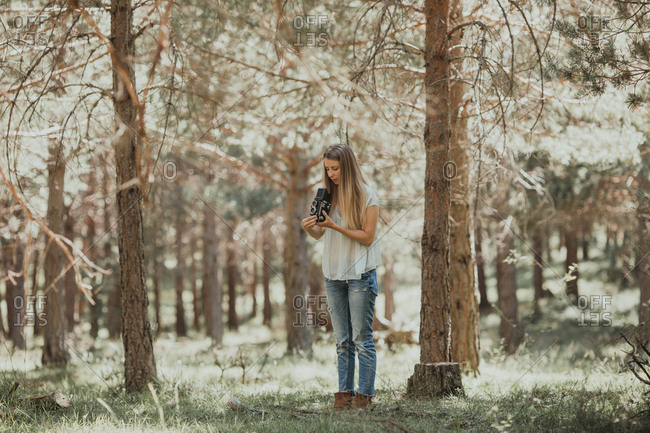 Woman with vintage camera in woods