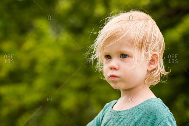 Blonde toddler boy in outdoor setting