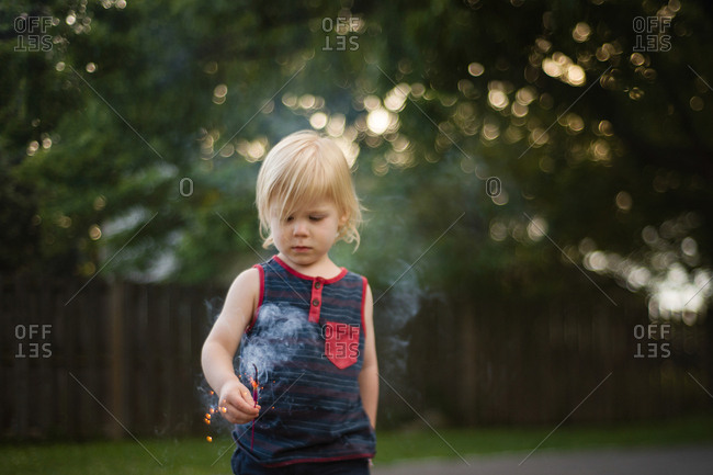 Toddler boy in yard with sparkler