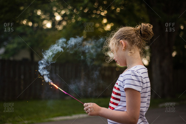 Girl in summer yard with sparkler