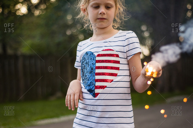 Girl watching a sparkler outside