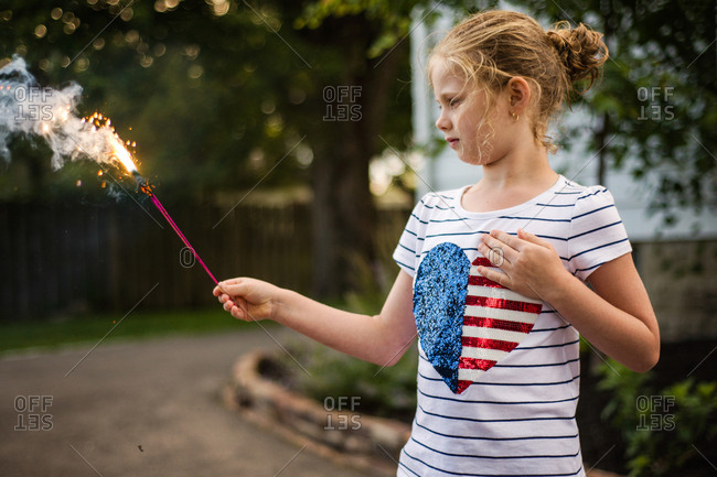 Girl looking at a lit sparkler