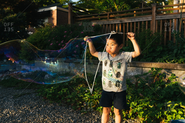 Little boy blowing a giant bubble through a string bubble maker
