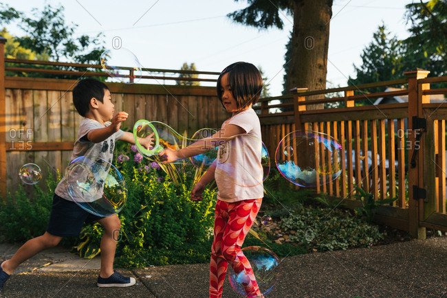Sister and brother making bubbles with large bubble wands in a backyard