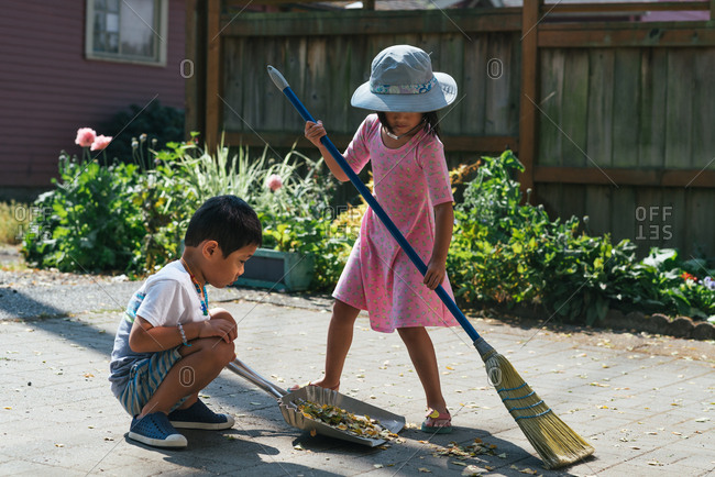 Brother and sister sweeping up leaves together on a patio