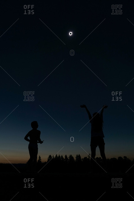 Silhouette of two children standing outdoors during a total solar eclipse
