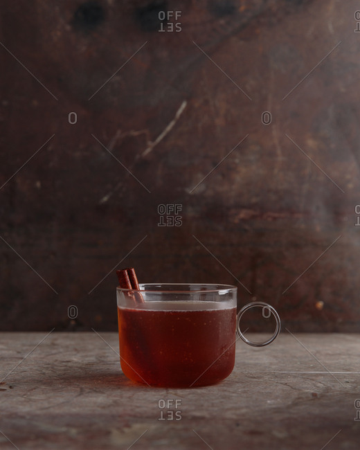 Tea inspired cocktail served in glass teacup with cinnamon sticks