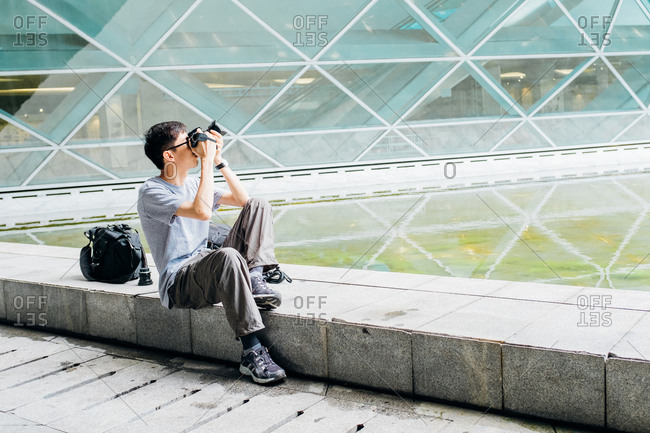 Asian man take photo outdoor in city