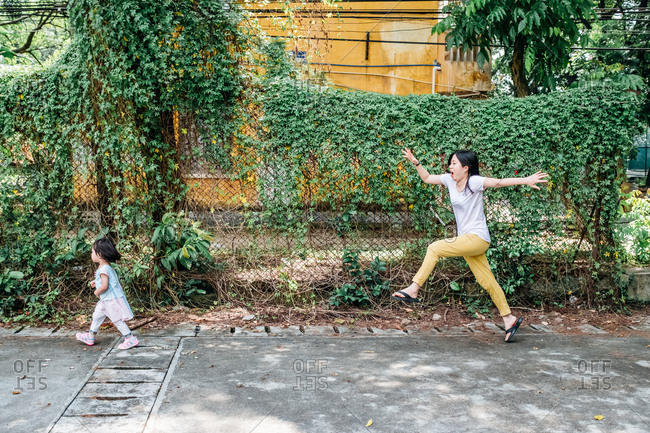 Asian mother running after her daughter